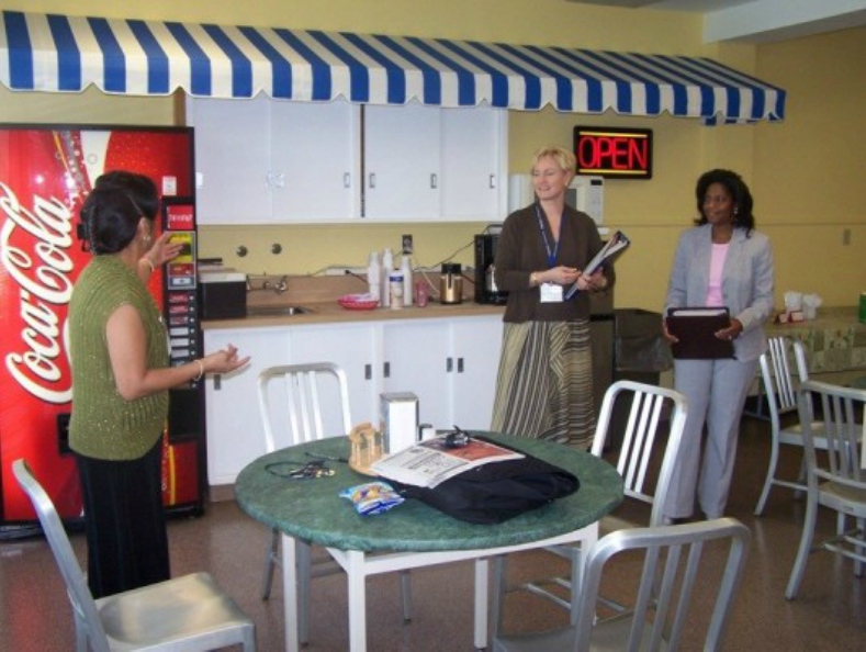 Three people standing in the DCS cafeteria, next to a table and chairs, with a soda vending machine in the background.