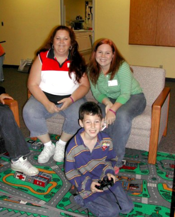 Two adults sitting on a couch, and a student sitting on an area rug holding a video game controller.