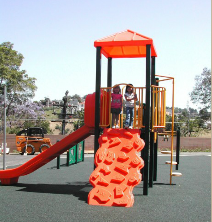 Two students standing on the top level platform of the play structure. There is a climing ramp, circle steps, and a slide coming from the top level.